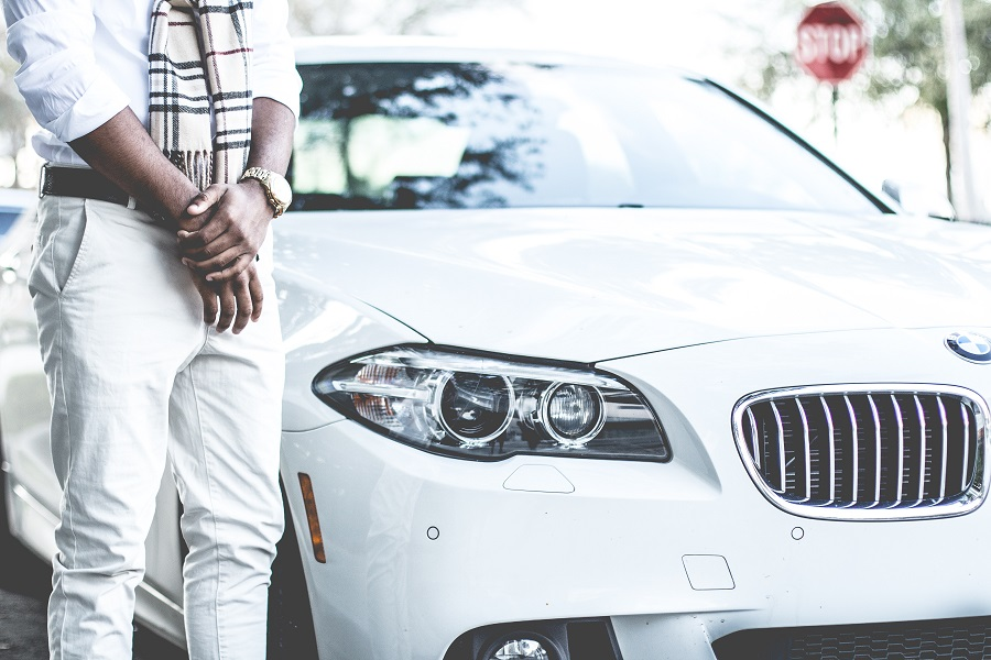 man standing next to white BMW with auto insurance in Omaha, NE