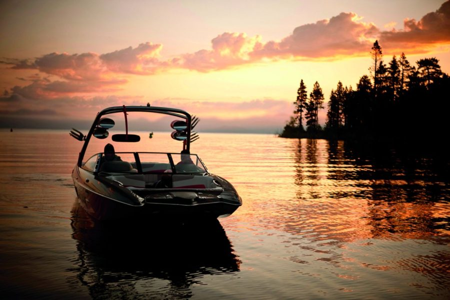 Boat sitting on lake at sunset, covered by recreational insurance