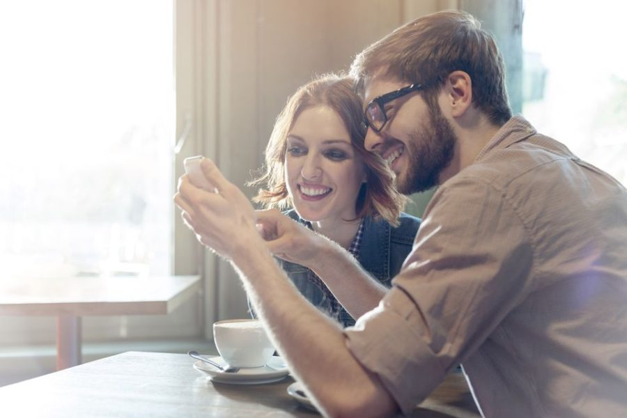 Couple drinking coffee and planning life insurance on iphone