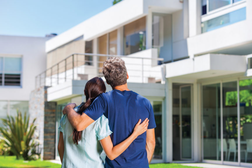 couple embracing in front of new big modern house covered by home warranty