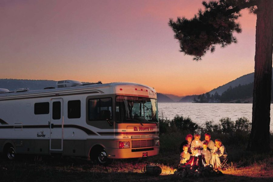 family camping with rv next to lake